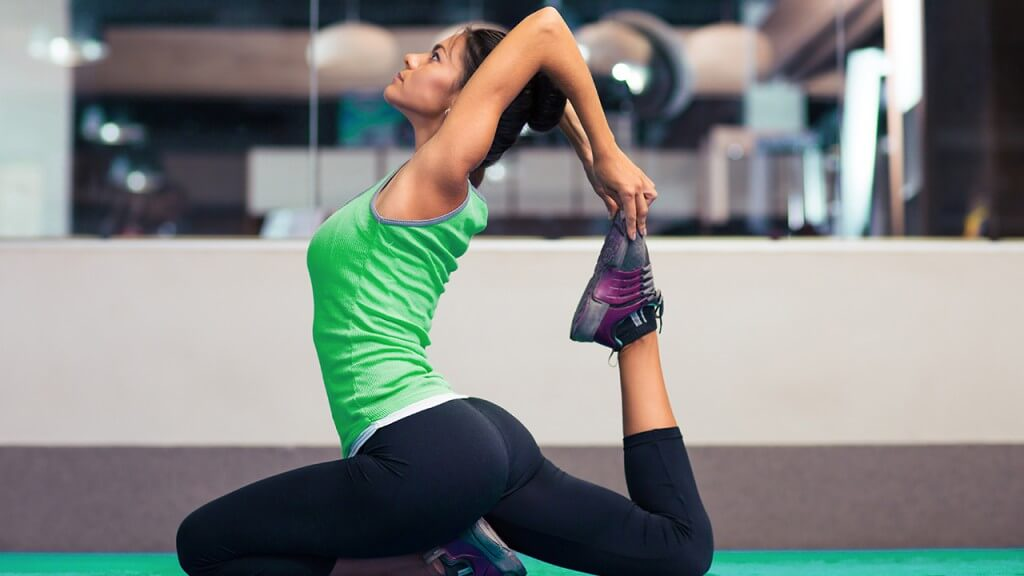 Portrait of a young woman stretching in gym